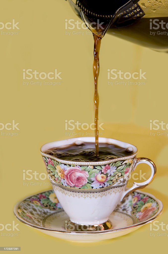 Floral-banded cup & saucer coffee pours stock photo