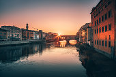 Famous view of Ponte Vecchio bridge, Arno river and  Palazzo Vecchio in the background at sunrise time in Florence, Tuscany, Italia