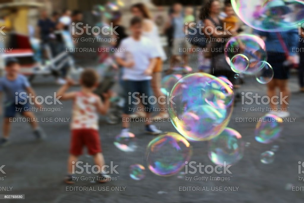 31/05/2017., Florence, Italy; Children running after soap bubbles on the town square stock photo