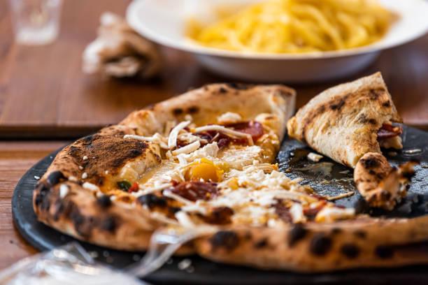 Florence, Itália Firenze Centrale Mercato mercado central com close-up de mesa de jantar com fatias inteiras de pizza e queijo comida tradicional - foto de acervo