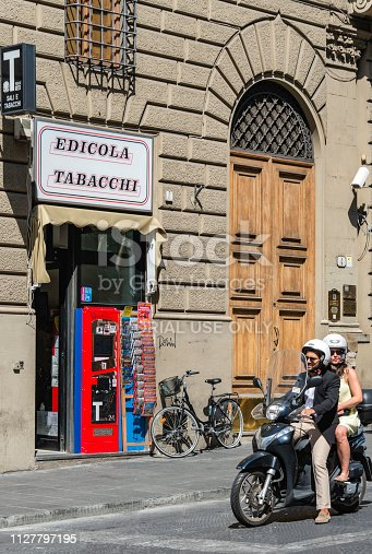 Two people on a motor scooter by a tobacco shop in the old town section of historic Florence, Italy.