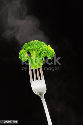 istock Floret of steaming broccoli held aloft on stainless steel fork 1205917783