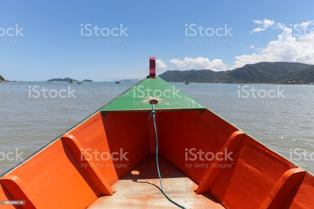 Florianopolis, Santa Catarina, Brazil. Wooden boat bow painted orange and green with beautiful sea and islands in the background. stock photo