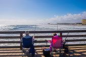 Retired couple fishing on the Daytona Beach Pier, one of the main tourist landmarks of this city of Florida.