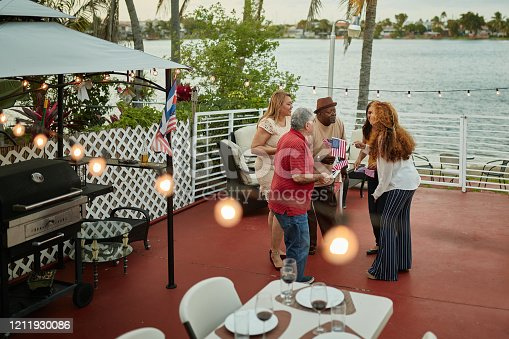 Elevated view of Hispanic and African-American friends in 50s, 60s, and 70s holding US flags and talking during holiday celebration on rooftop balcony.