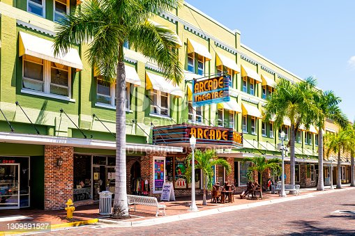 Fort Myers, USA - April 29, 2018: Florida Gulf of Mexico city street with retro vintage neon sign for Arcade theatre theater building with shops stores