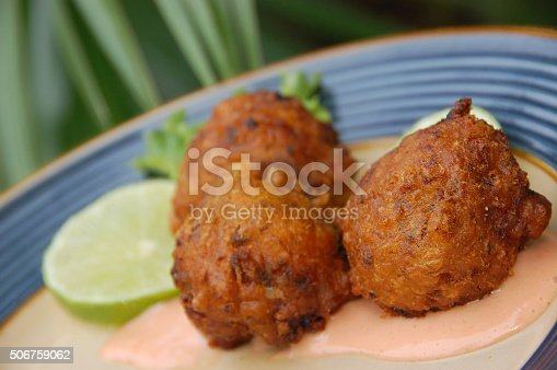 Three deep fried conch fritters, a specialty of the Florida Keys, served with lime and dipping sauce.