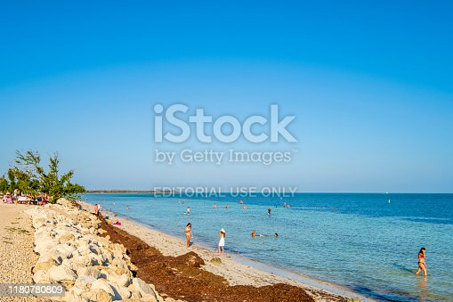 Tourists relaxing in the clear and shallow waters lapping Loggerhead Beach in the Bahia Honda State Park, lower Florida Keys.