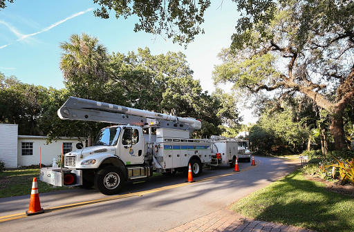 Florida Power and Light trucks parked on a residential street