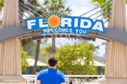 istock Florida southern town city welcome center at border with Alabama and visitor center and back of young man looking at sign 1154583559