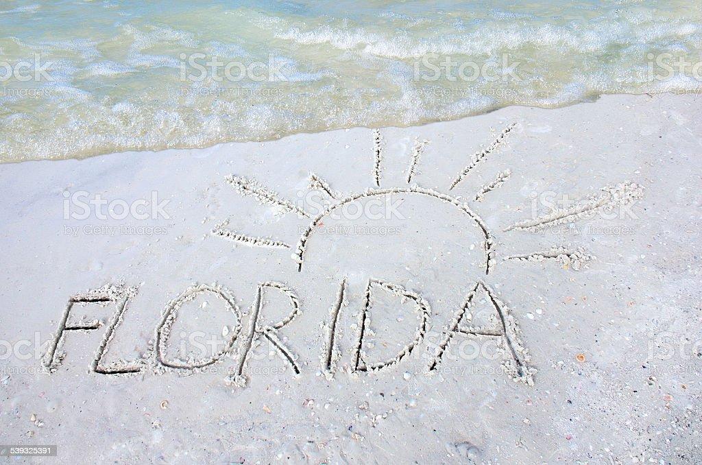 Florida sol desenhada na areia na praia com uma onda - foto de acervo