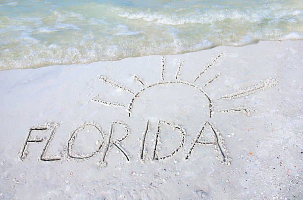Florida sun drawn in sand on beach with a wave stock photo