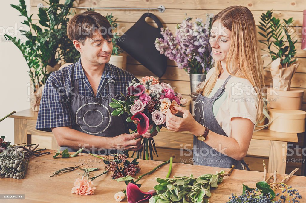 Small business. Male and female florists making rose bouquet in...