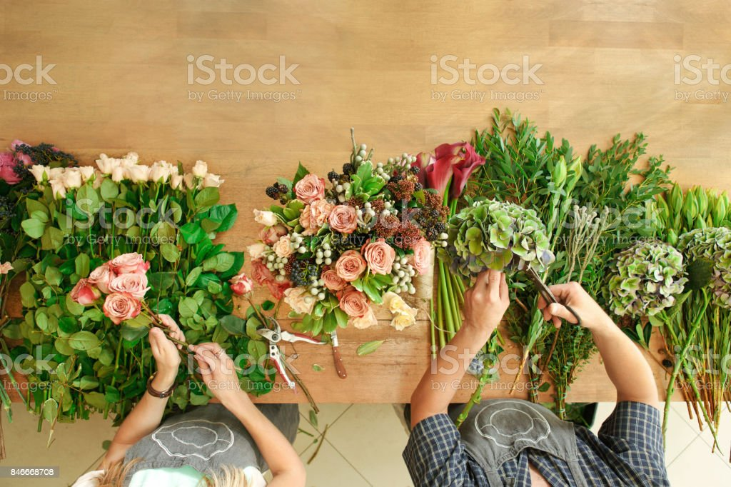 Florist and assistant in flower shop delivery make rose bouquet, table top view