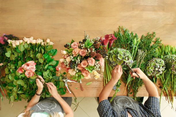 floristen und assistent im blumenversand shop machen rose bouquet, tabelle draufsicht - blumenarrangement stock-fotos und bilder