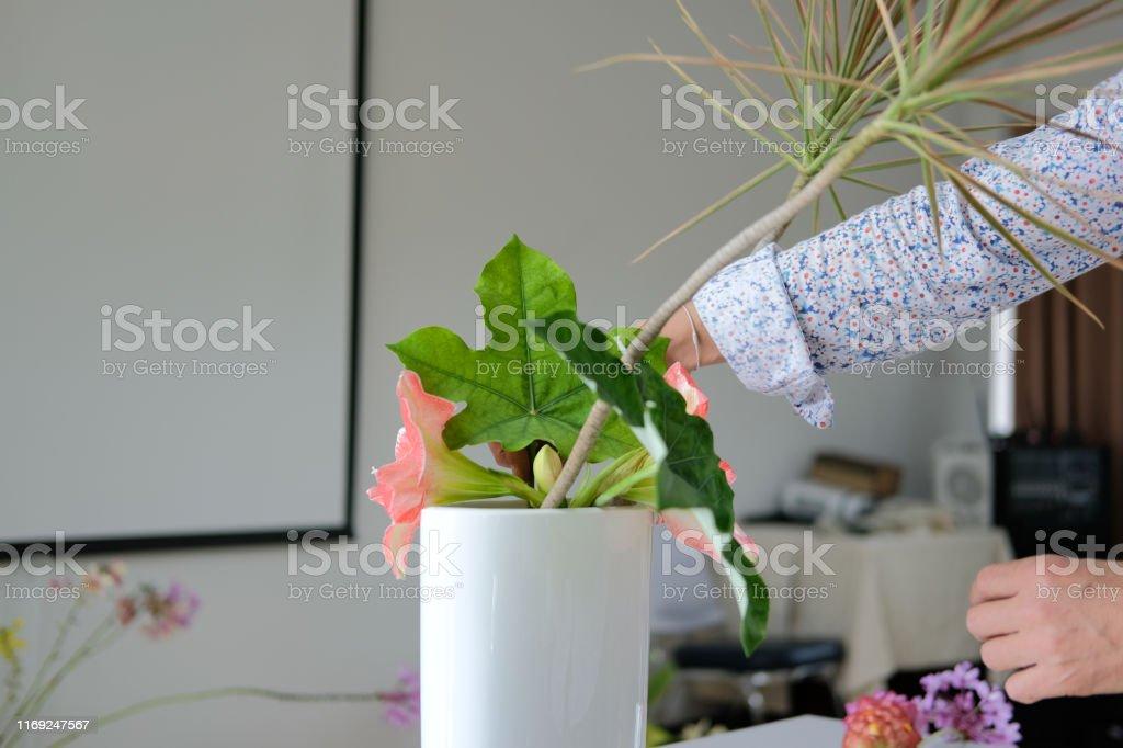 florist arranging flower bouquet in vase. teacher teaching floristry...