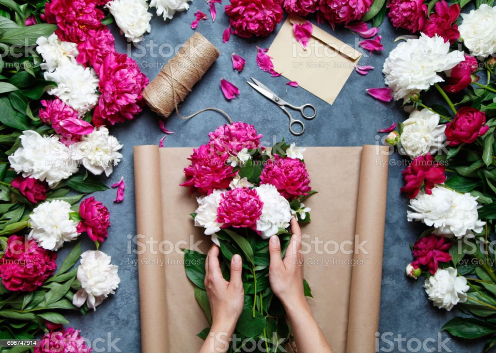 Florist at work: pretty woman making summer bouquet of peonies on a working gray table. Kraft paper, scissors, envelope on the table. View from above. Florist at work: pretty woman making summer bouquet of peonies on a working gray table. Kraft paper, scissors, envelope for congratulations on the table. View from above. Flat lay composition. Adult Stock Photo