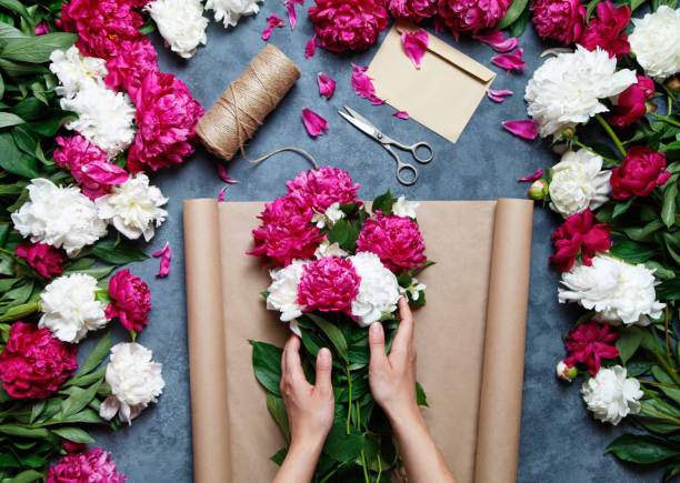 Florist at work: pretty woman making summer bouquet of peonies on a working gray table. Kraft paper, scissors, envelope on the table. View from above. stock photo