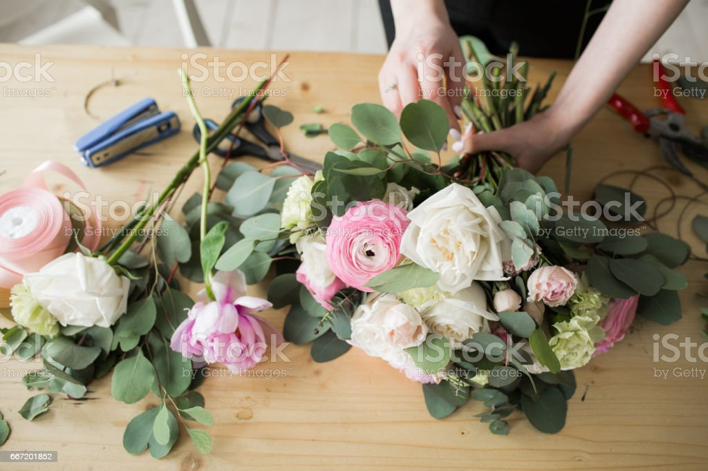 Florist at work: pretty young woman making fashion modern bouquet of different flowers Florist at work: pretty young woman making fashion modern bouquet of different flowers. Adult Stock Photo