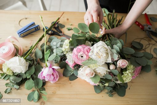 Florist at work: pretty young woman making fashion modern bouquet of different flowers.