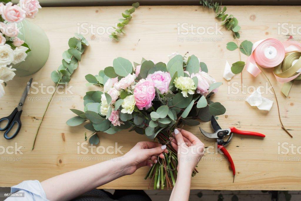 Fleuriste au travail: jolie jeune femme faisant le bouquet moderne fashion de différentes fleurs - Photo de Adulte libre de droits