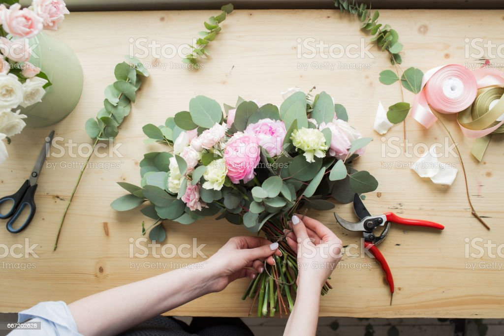 Florist at work: pretty young woman making fashion modern bouquet of different flowers – zdjęcie