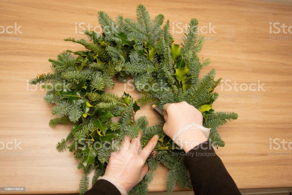 woman making natural Christmas wreath, christmas decorations
