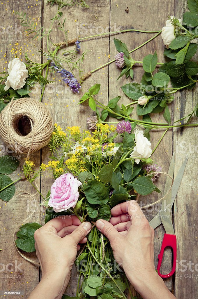 Florist at work. Woman making summer floral decorations stock photo