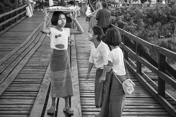 florist child sell flowers for buddha on the wood bridge - little girls giving head stock photos and pictures