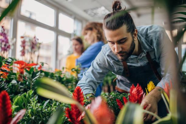 un employé de fleuriste et un jeune invité - fleuriste photos et images de collection
