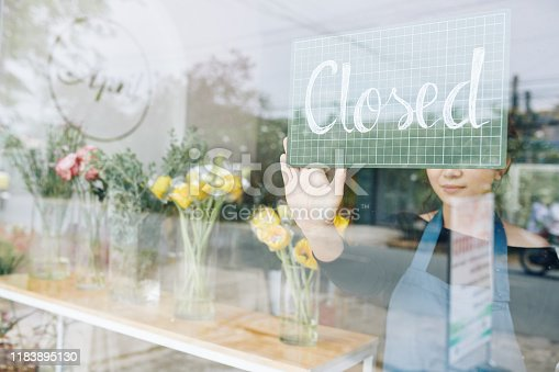Florist hanging plastic board on glass door when closing her store in the evening