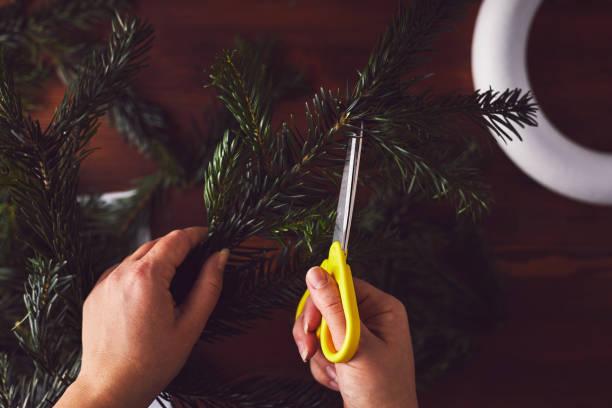 blumengeschäft schneiden zweig für die dekoration von der weihnachtskranz - eco bastelarbeiten stock-fotos und bilder