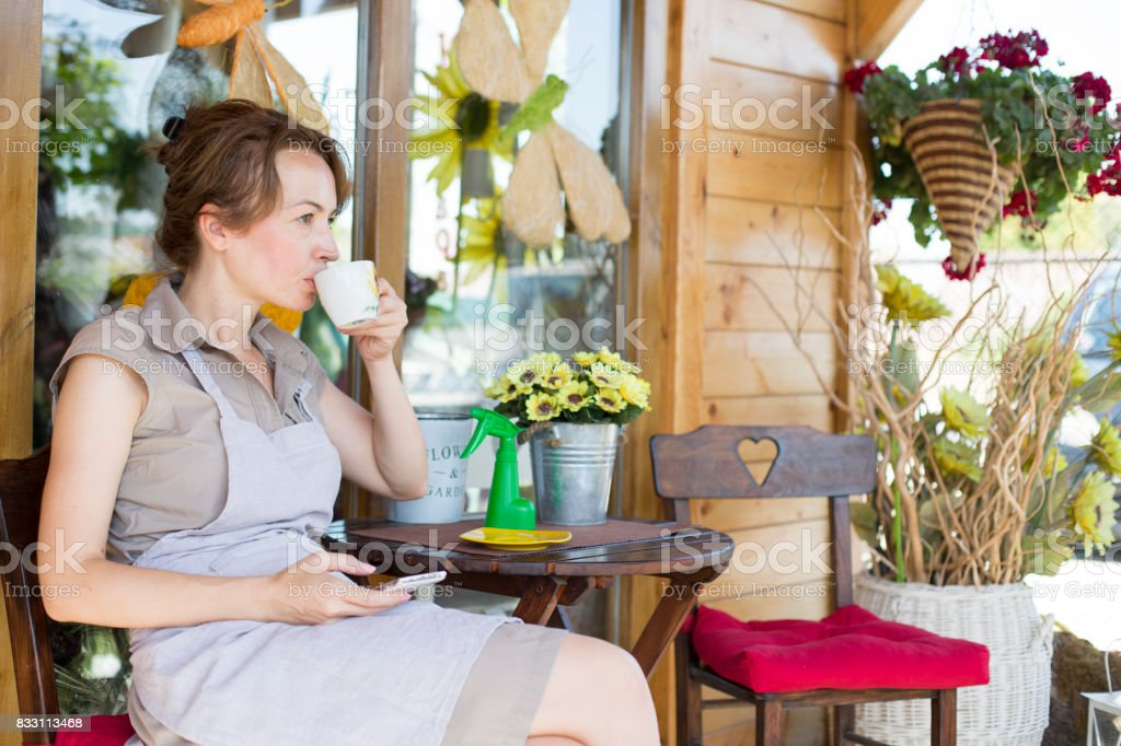 Florist drinking coffee in garden stock photo