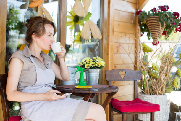 Florist drinking coffee in garden stock photo