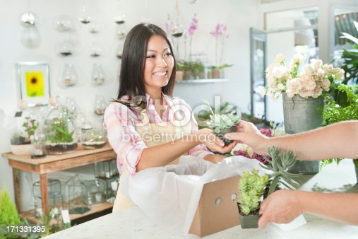 A small business owner of a retail flower shop. An Asian woman florist entrepreneur shopkeeper. She is working behind the checkout counter in her shop serving a female customer with her purchases , surrounded by products, merchandize and flower display in the background. Photographed in horizontal format.