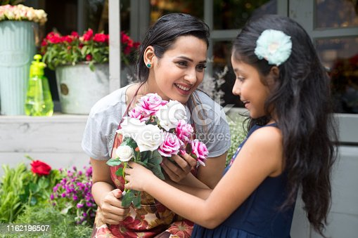 Happy woman florist giving rose to girl at flower shop