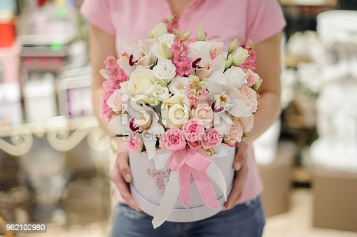 istock Florist holding a white flower box with flower composition in pink and white tones consisting of roses and other beautiful flowers 962102980