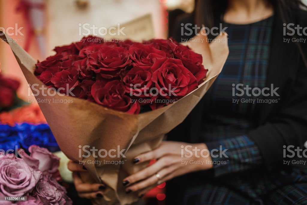 Florist holding arranged bouquet of red roses in the flower shop