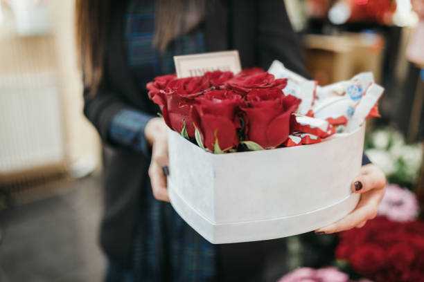 Florist holding flower arrangement of red roses stock photo