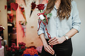 Florist holding red roses in the flower store