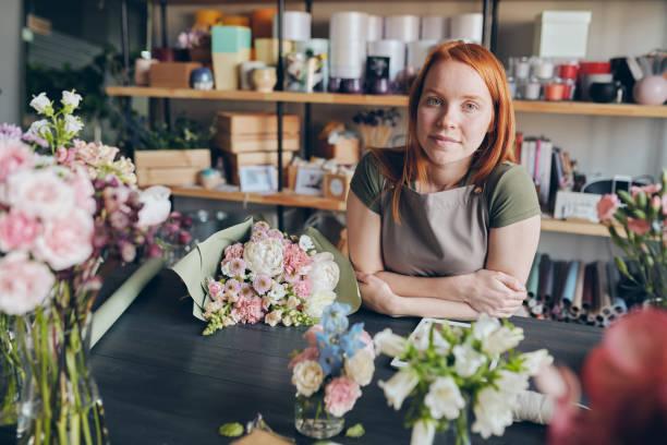 Florist in Schürze steht am Tresen – Foto