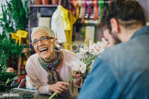 Female florist laughing at a counter table with a flower in her hand
