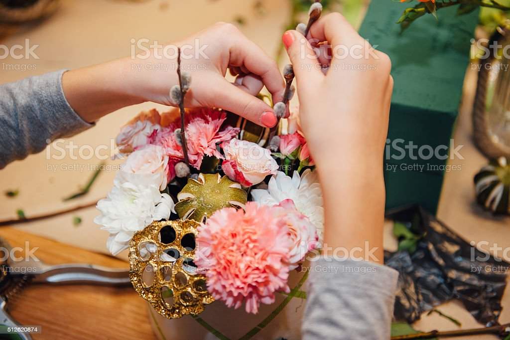 florist makes a box with different flowers stock photo