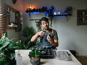 Hipster asian man watering and seeding his indoor plant garden.