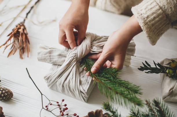 ゼロ廃棄物クリスマスプレゼントを準備する花屋。プラスチックフリーの休日。松ぼっくりとベリーと白い素朴なテーブルの上に緑のモミの枝とリネン生地でスタイリッシュなクリスマスプ� - sustainability ストックフォトと画像