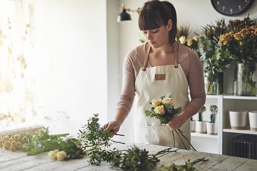 Florist putting together a mixed flower arrangement in her shop