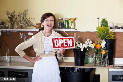 Young woman in florist shop holding an Open sign