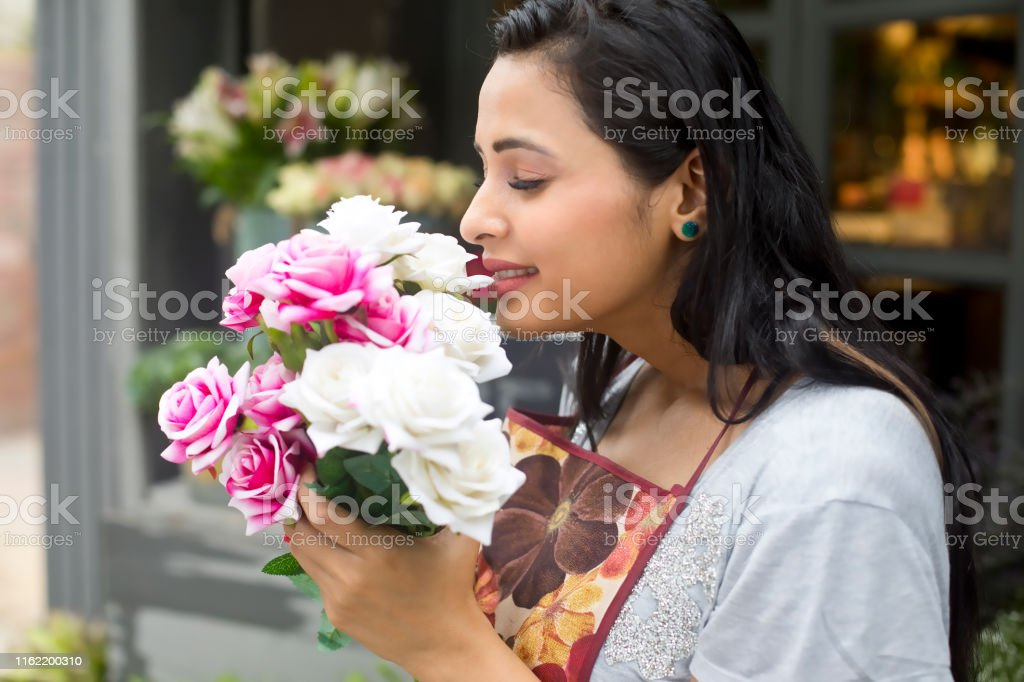 Beautiful woman florist smelling a bouquet of rose flowers