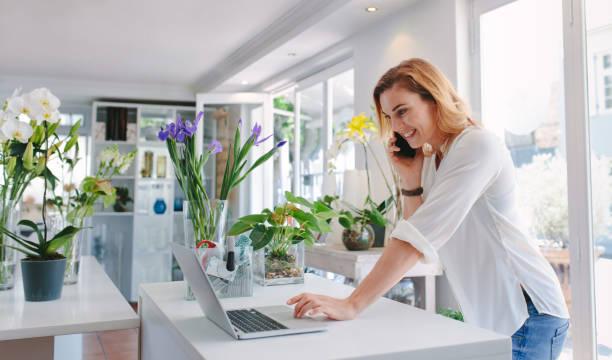 fleuriste prenant commande sur téléphone mobile - fleuriste photos et images de collection