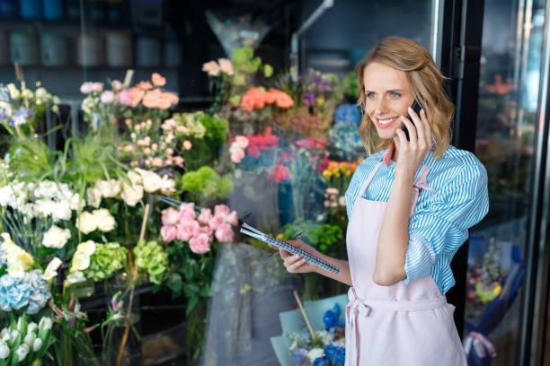 florist talking on smartphone - owner laptop smartphone foto e immagini stock